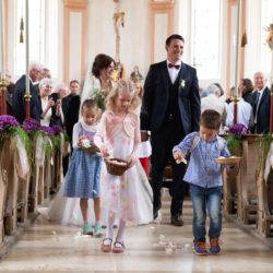 Hochzeitsfotografie: Ein Brautpaar Und Kinder Gehen Durch Den Mittelgang Einer Kirche