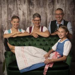 Familienfotografie: Familie In Tracht (3 Personen) Schaut Hinter Einem Grünem Sofa Hervor, Ein Mädchen Liegt Auf Dem Sofa.